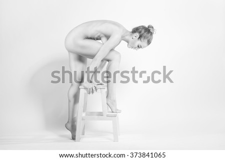 Athletic European fashion model woman with shiny curly hair, awesome gorgeous slim body and perfect skin is sitting on the chair nude in studio for bodycare and wellness adverisement - stock photo