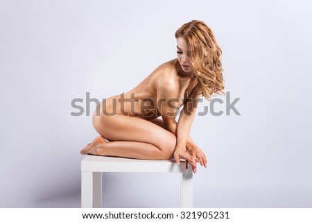 Athletic European fashion model woman with shiny curly red hair, awesome gorgeous slim body and perfect skin is sitting on the table nude in studio for bodycare and wellness adverisement - stock photo