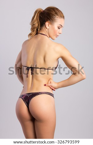 Athletic european fashion model woman with shiny healthy brunette hair, awesome gorgeous slim body and perfect skin, fitness bikini in studio for bodycare and wellness advertisement - stock photo