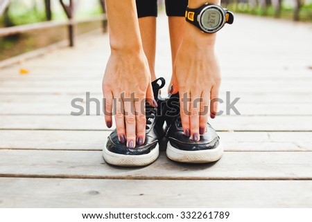 Athletic fit girl stretching in park in summer after training workout before run. Smart watch pulse meter on hand. Touching toes to stretch well. Front view central orientation - stock photo