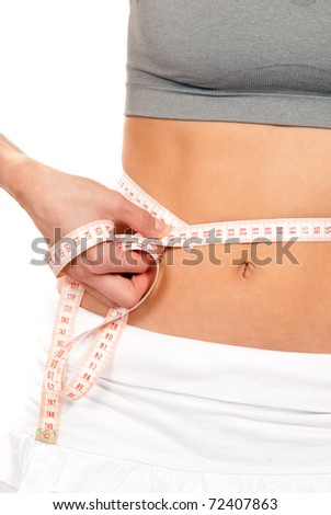 Athletic fit slim woman measuring her waist around metric tape measure after a fitness diet  isolated over white background - stock photo