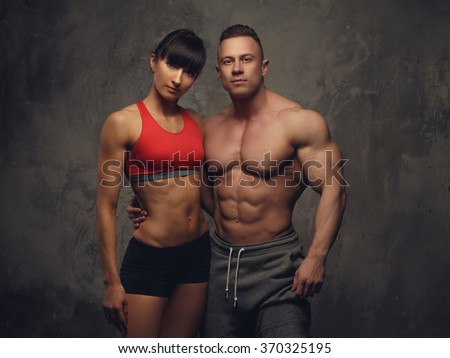 Athletic fitness couple. Shirtless bodybuilder and his fitness girlfriend. - stock photo