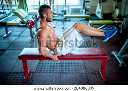 athletic fitness man working the abdomen at gym - stock photo