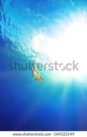 athletic girl diving under the sea