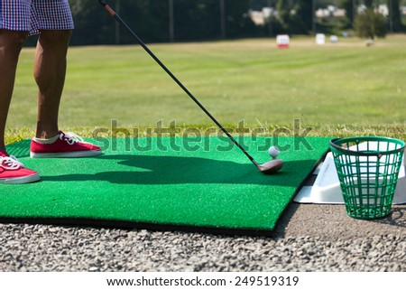 Athletic golfer swinging at the driving range dressed in casual attire - stock photo