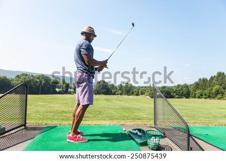 Athletic golfer teeing up at the driving range dressed in casual attire. - stock photo