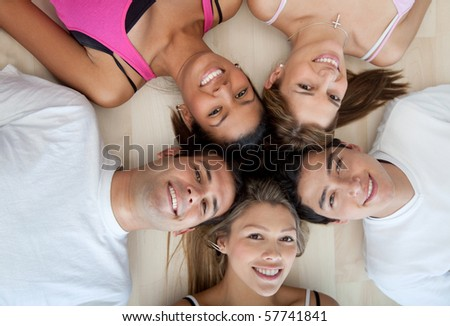 Athletic group of people lying on the floor with heads together