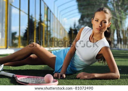 athletic healthy girl lying on the grass and resting after tennis outdoors - stock photo