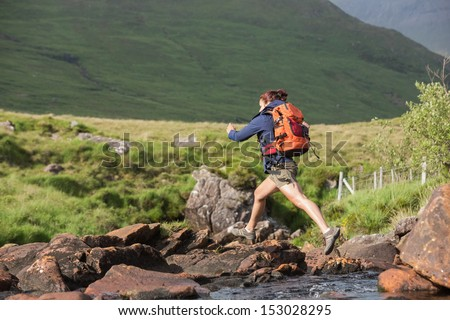Athletic hiker leaping across rocks in a river in the countryside - stock photo