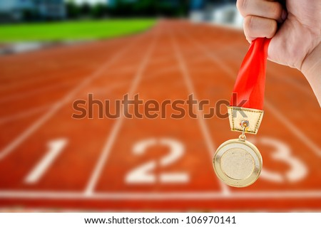 Athletic holding golden medal in Start Running track - stock photo