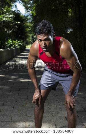 Athletic Indian man having a break from running. Asian Runner jogging in the park. Male fitness concept. - stock photo
