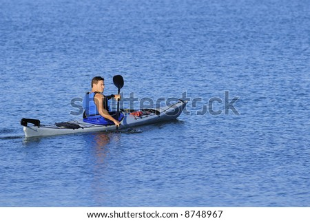 Athletic kayaker rows off into calm blue waters of Mission Bay, San Diego, California, looking over his shoulder. Plenty of copyspace around him