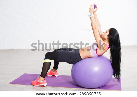 Athletic long hair brunette girl in sportswear lying on fitball and doing exercises with dumbbells. On white concrete wall background.