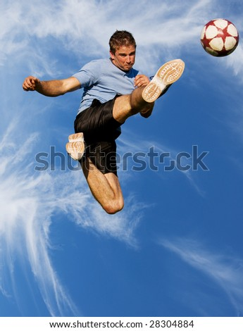 Athletic male high in the air kicking a soccer ball - stock photo