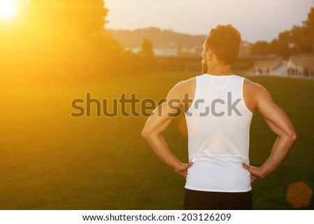 Athletic male runner standing in the park and looking at sunset, muscular sportsmen resting during sunset ,health lifestyle and fitness concept, evening jogging - stock photo