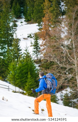 athletic male with a backpack walking on snow. winter holidays in the mountains. The Ukrainian Carpathians.