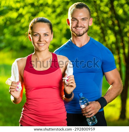 Athletic man and woman after fitness exercise. Beautiful young couple in sports clothing after outdoor exercises. White towel. - stock photo