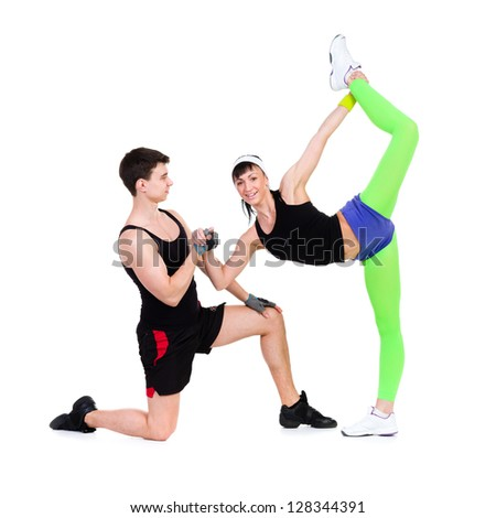 Athletic man and woman doing fitness exercise against isolated white background - stock photo