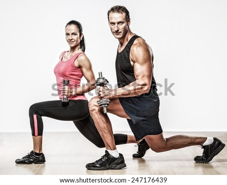 Athletic man and woman with a dumbbells - stock photo