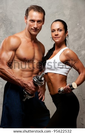 Athletic man and woman with a dumbbells. - stock photo
