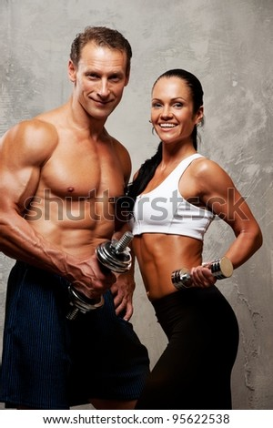 Athletic man and woman with a dumbbells.