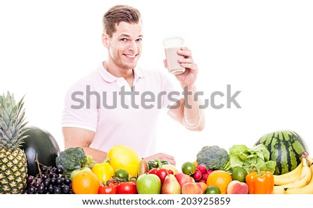 Athletic man drinking a protein shake behind a table full of vegetables and fruits - isolated on white background - stock photo