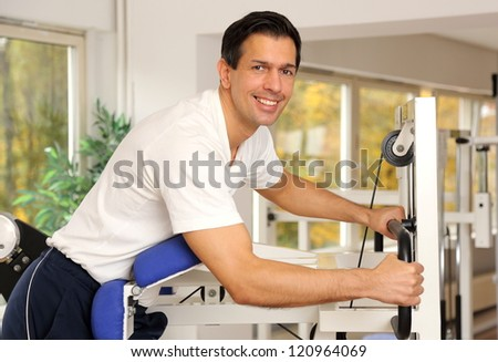 Athletic man exercising and lifting weights in a fitness center - stock photo