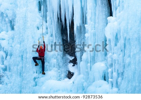 Athletic man in red coat with orange helmet and gold ice tools climbing a large blue wall of ice at the Ouray Ice Park - stock photo