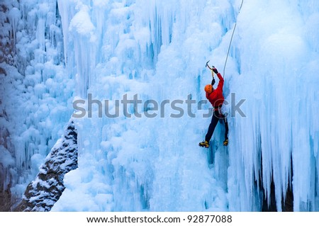 Athletic man in red coat with orange helmet and gold ice tools climbing a large blue wall of ice in the Uncomphagre Gorge - stock photo