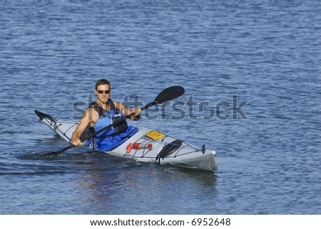 Athletic man is showing off his kayaking skills at Mission Bay, San Diego under a warm light of late summer afternoon.
