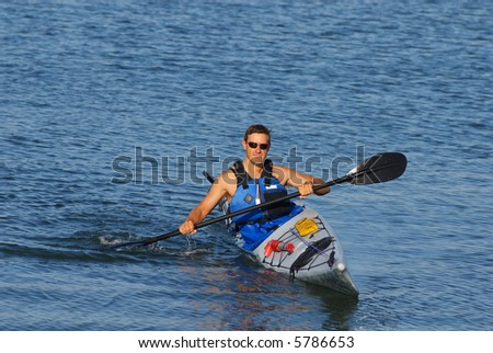 Athletic man is showing off his mastery of kayaking at Mission Bay, San Diego under a warm light of late summer afternoon. - stock photo