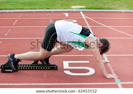 Athletic man on the starting line putting his foot in the starting block  in a stadium - stock photo