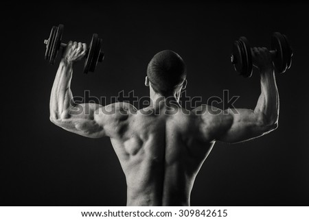 Athletic man posing with dumbbells on a black background. Strained muscles. Weight training for the muscles of the body. The success achieved by the efforts and work on them. - stock photo
