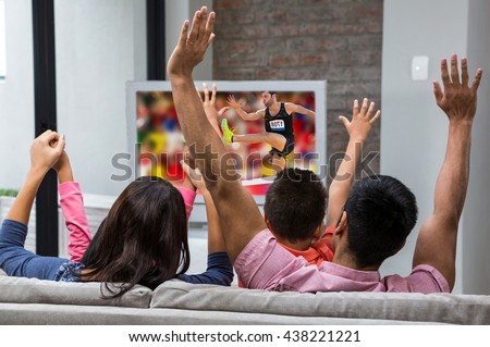 Athletic man practicing show jumping against happy family rejoicing while watching tv on the sofa - stock photo