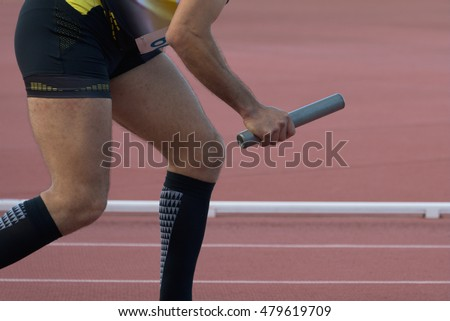 Athletic man running a relays the athletics track