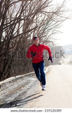 Athletic  man running in winter day - stock photo
