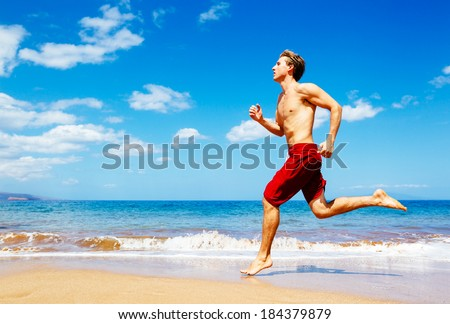 Athletic Man Running on Beach - stock photo