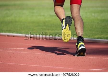 Athletic man running on track - stock photo