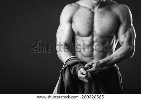 Athletic man showing muscles in suspense on a black background