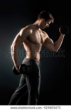 Athletic man showing muscular body and doing exercises with dumb