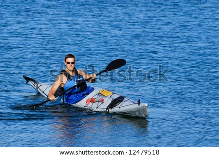 Athletic man showing off his mastery of sea kayak in blue calm waters of Mission Bay, San Diego, California.