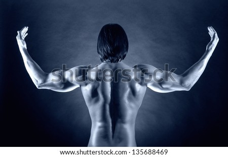 Athletic man shows his muscular back - stock photo