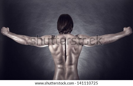 Athletic man shows his muscular back on a dark background - stock photo