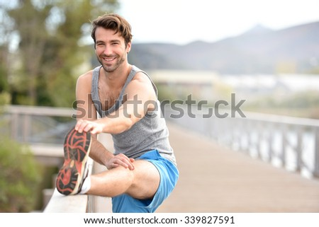 Athletic man stretching out after running