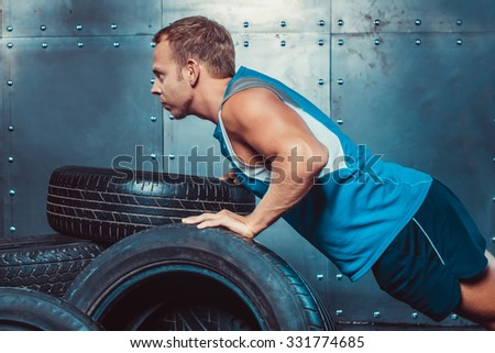 Athletic man trains, pushed from a car tire forward looking. concept of health and strength. - stock photo