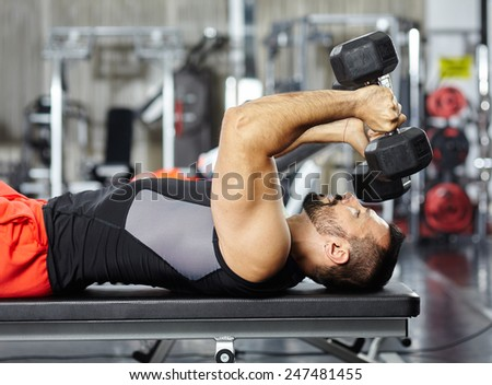 Athletic man working chest and triceps with dumbbells - stock photo