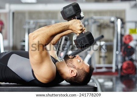 Athletic man working out his chest and triceps with heavy dumbbells in a gym - stock photo