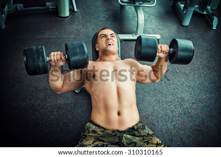 Athletic man working out with dumbbells in a gym.  - stock photo