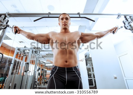 Athletic man working out with weight training equipment in a gym. Sports, bodybuilding. Healthy lifestyle.