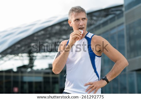Athletic Mature Man Eating Bar Of Chocolate And Listening Music In The Urban Center - stock photo